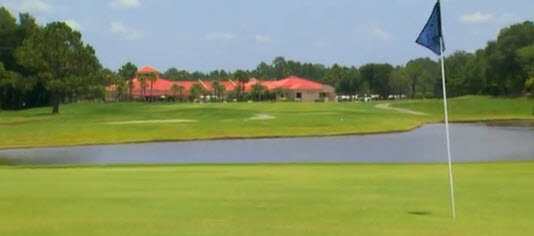 Green, lake and Clubhouse in background.